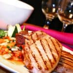 plate of grilled pork chops with vegetable side glasses in background
