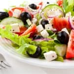 plate of salad made with lettuce, black olives, tomatoes, feta cheese