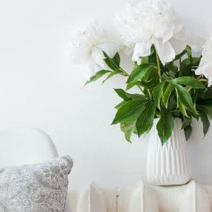 small white chair next to radiator with white flowers in a vase