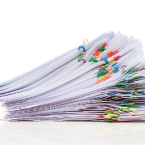 stack of paperwork with colorful paperclips