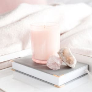 book, candle and rocks on breakfast tray placed on bed