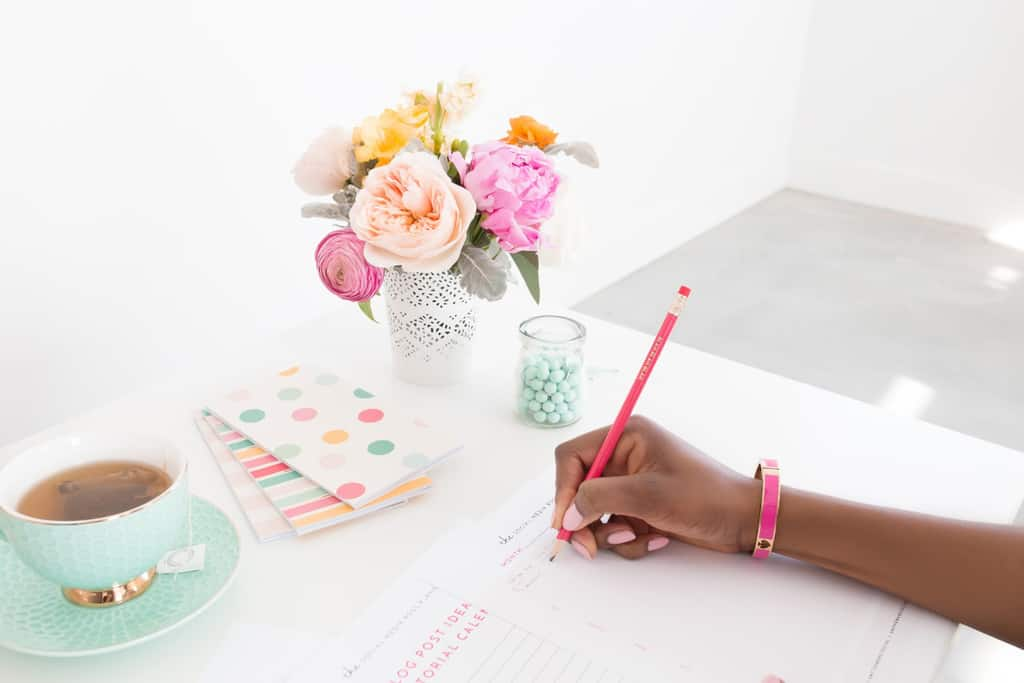 woman writing in planner flowers on desk-things people with clean houses do every day