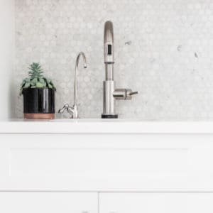 white counter top and back splash in a small kitchen with silver faucet and plant