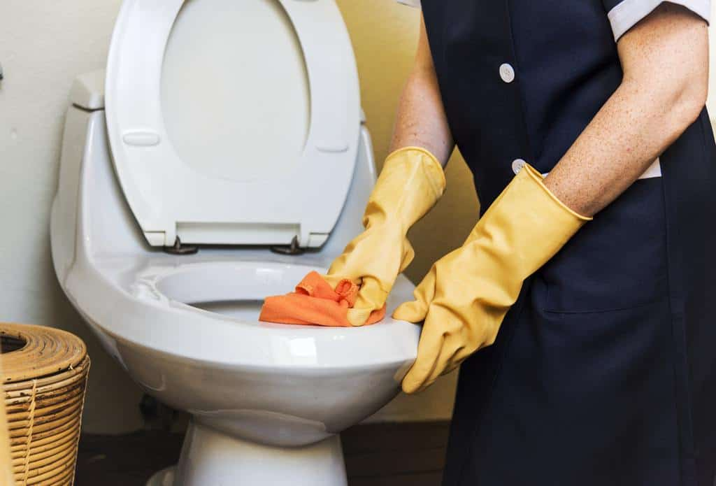 12 Professional Cleaning Tips-woman wearing gloves scrubbing toilet