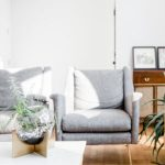 two gray small accent chairs behind coffee table with plant