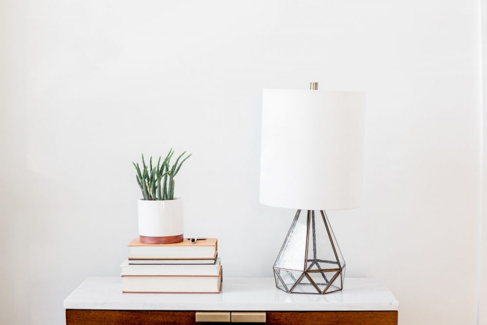simple side table with modern lamp, stack of books, and plant