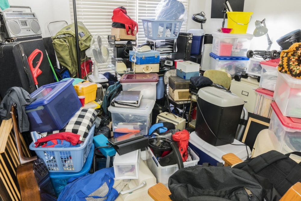 Hoarder room packed with stored boxes, electronics, files, business equipment and household items.