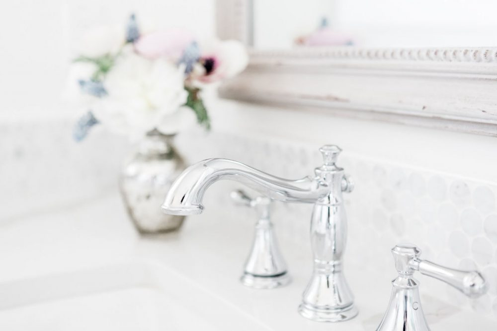 bathroom sink with sparkling silver faucet. Mirror and vase of flowers in background.