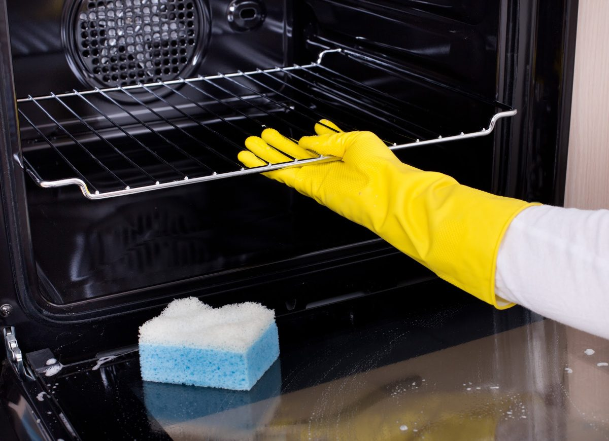 Things you forget to clean-Close up of female hand with yellow protective gloves cleaning oven