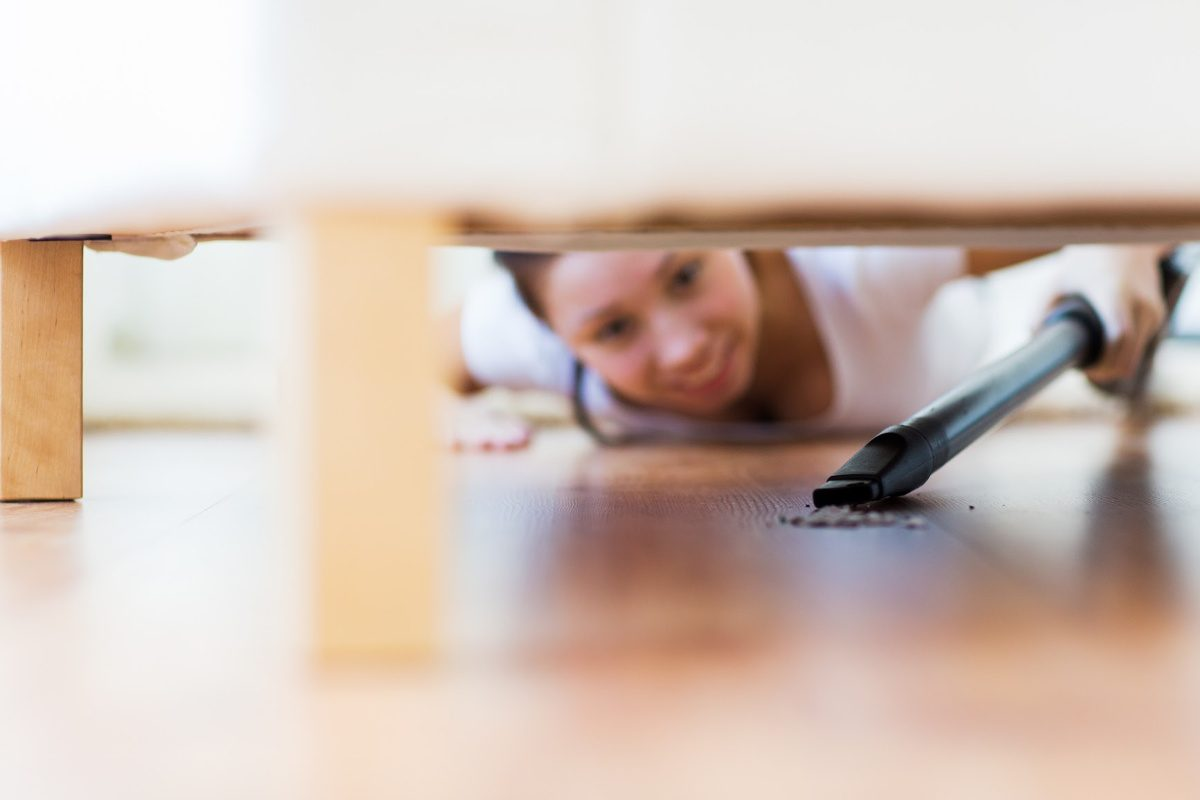 Things you forget to clean-woman vacuuming  under couch