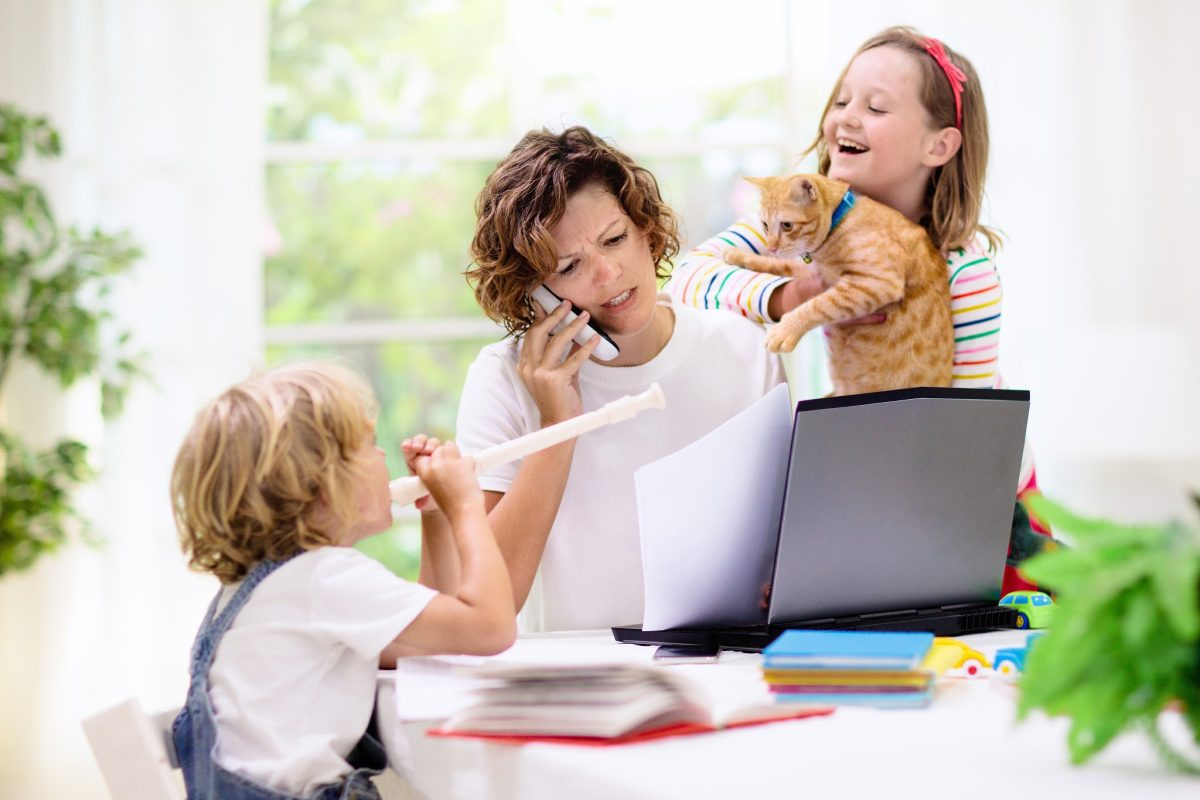 productivity tips- woman working from home with distractions of kids, pets, and noise